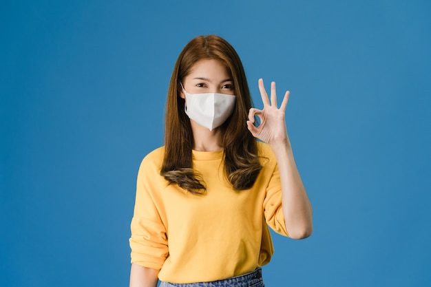 Giovane ragazza asiatica che indossa la maschera facciale medica gesticolando segno ok con vestito in un panno casual e guarda la telecamera isolata su sfondo blu. autoisolamento, allontanamento sociale, quarantena per il virus corona.