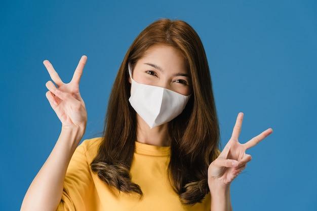Giovane ragazza asiatica che indossa la maschera medica che mostra il segno di pace, incoraggiare con vestito con un panno casual e guardando la telecamera isolata su sfondo blu. allontanamento sociale, quarantena per il virus corona.