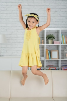 Giovane ragazza asiatica che salta sul divano di casa e ridendo