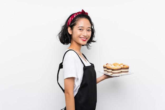 Giovane ragazza asiatica che tiene i lotti della torta del muffin che sorride molto