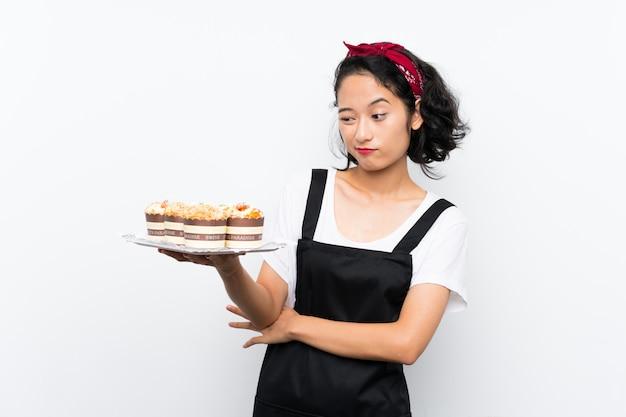 Giovane ragazza asiatica che tiene i lotti della torta del muffin