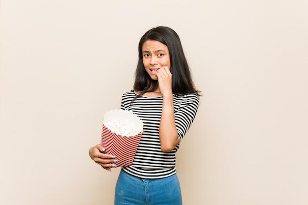 Giovane ragazza asiatica che tiene le unghie mordaci di un secchio del popcorn, nervose e molto ansiose.