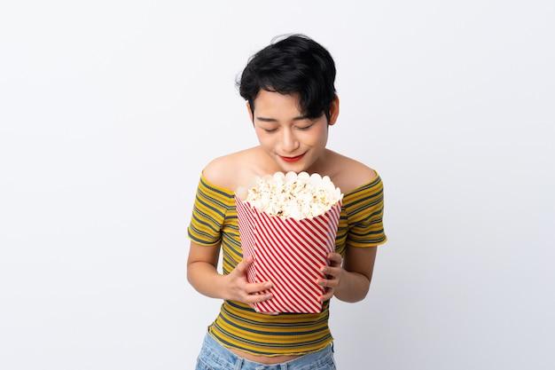 Giovane ragazza asiatica che tiene un grande secchio di popcorn