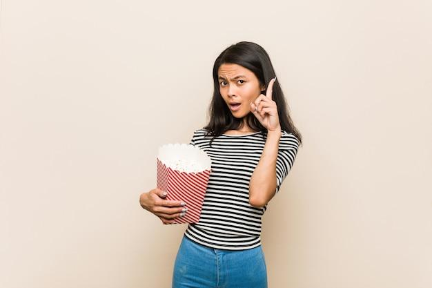 Giovane ragazza asiatica che tiene un secchio del popcorn che ha una certa grande idea, concetto di creatività.