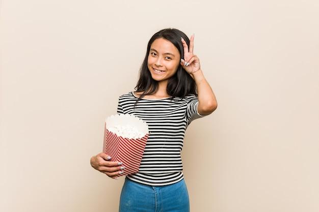 Giovane ragazza asiatica che tiene un secchio del popcorn che mostra il segno di vittoria e che sorride ampiamente.