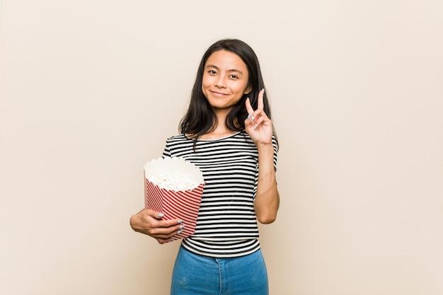 Giovane ragazza asiatica che tiene un secchio del popcorn che mostra numero due con le dita.