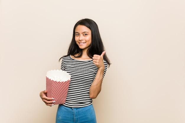 Giovane ragazza asiatica che tiene un secchio del popcorn che sorride e che alza pollice in su