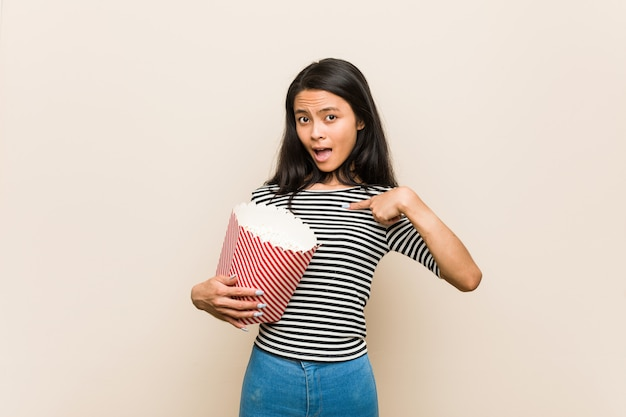 Giovane ragazza asiatica che tiene un secchio di popcorn sorpreso indicando se stesso, sorridendo ampiamente.