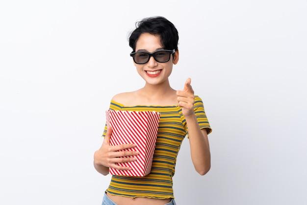 Giovane ragazza asiatica con gli occhiali 3d e in possesso di un grande secchio di popcorn mentre punta davanti