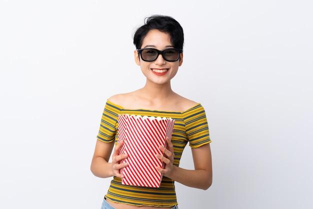 Giovane ragazza asiatica con gli occhiali 3d e in possesso di un grande secchio di popcorn
