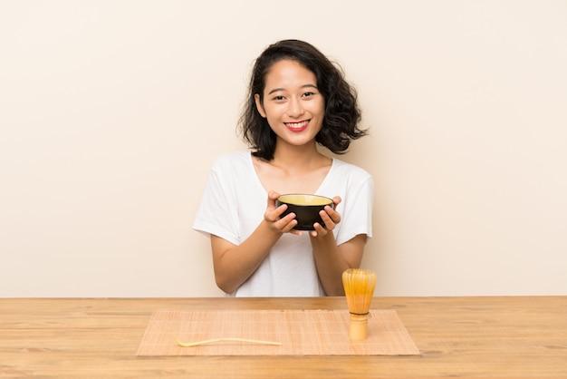 Giovane ragazza asiatica con il matcha del tè