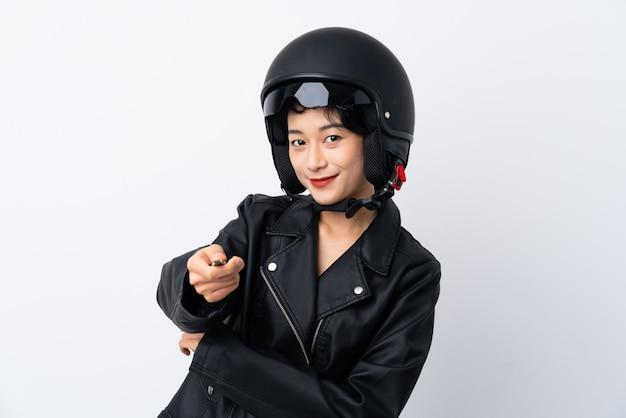 Giovane ragazza asiatica con un casco del motociclo e una chiave sopra la parete bianca isolata