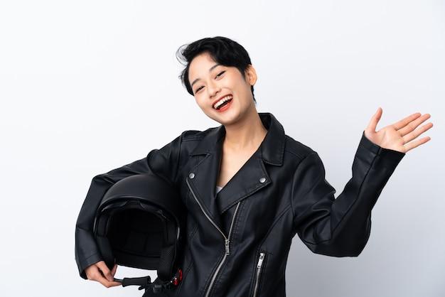 Giovane ragazza asiatica con un casco del motociclo sopra la parete bianca isolata che saluta con la mano con l'espressione felice