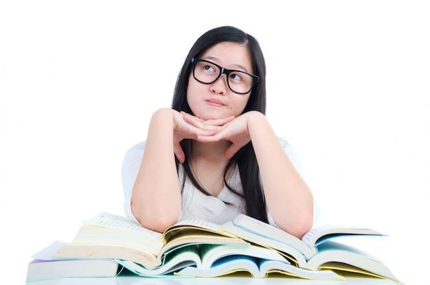 Giovane ragazza asiatica dello studente che pensa con il libro sopra fondo bianco