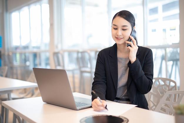 Giovane ragazza asiatica di affari che lavora con il computer portatile nel caffè della caffetteria.
