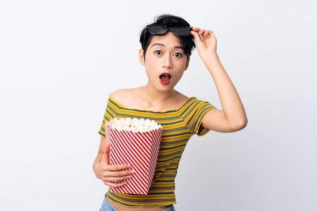 Giovane ragazza asiatica sorpresa con gli occhiali 3d e in possesso di un grande secchio di popcorn