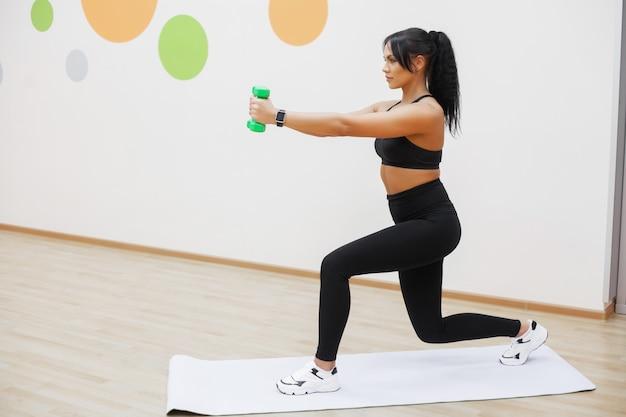 Giovane ragazza atletica con manubri al chiuso, allenamento ragazza fitness in palestra