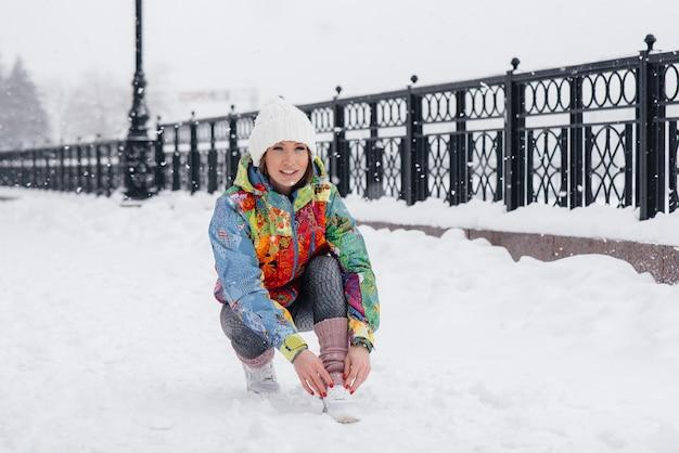 Giovane ragazza atletica lega le scarpe in una giornata gelida e nevosa. fitness, corsa