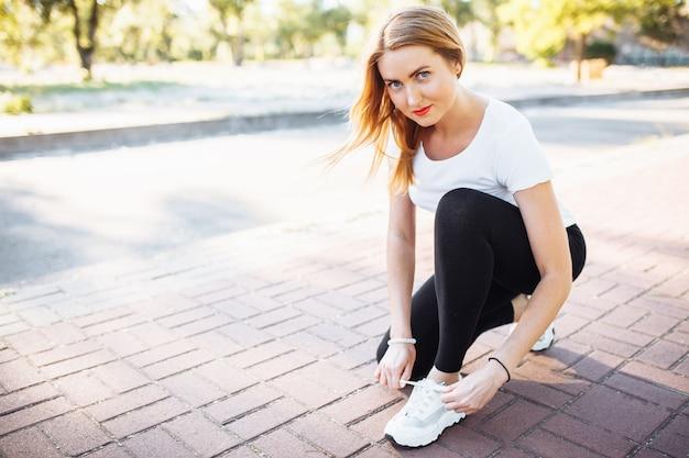 Giovane ragazza atletica, legando i lacci delle scarpe, prima di fare jogging