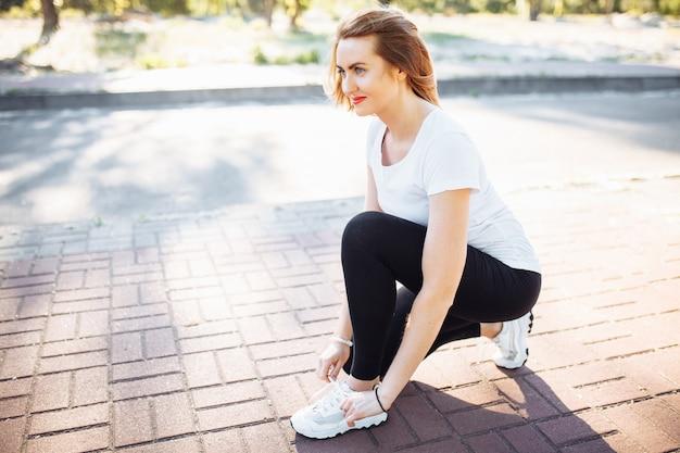 Giovane ragazza atletica, legare i lacci delle scarpe, prima di fare jogging, può essere utilizzata per la pubblicità, l'inserimento di testo