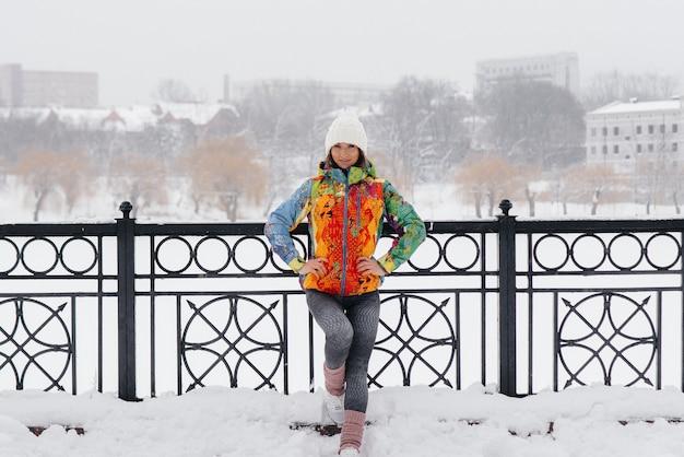 Giovane ragazza atletica pone in una giornata gelida e nevosa. fitness, corsa