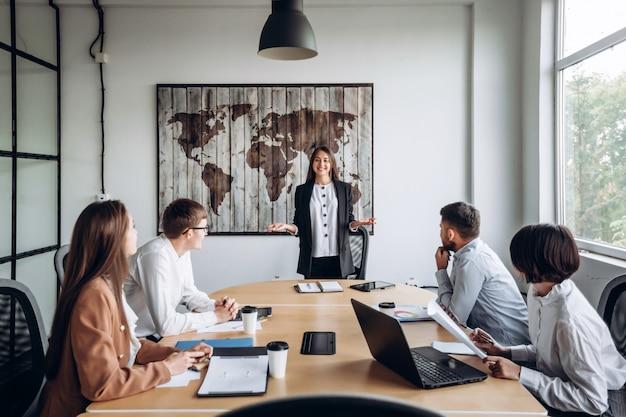 Giovane ragazza attraente che presenta una relazione davanti ai suoi colleghi. riunione di lavoro in ufficio