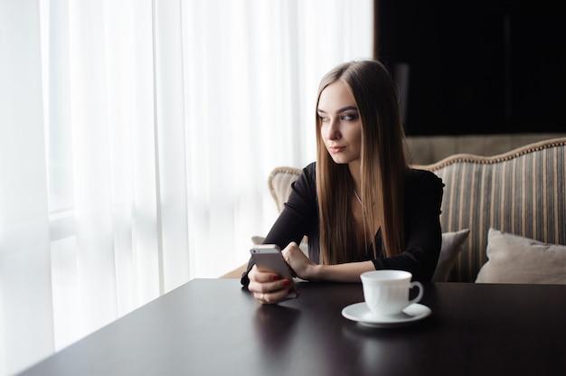 Giovane ragazza attraente che si siede da solo vicino alla grande finestra