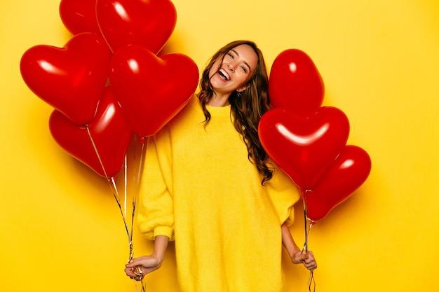 Giovane ragazza attraente con capelli ricci lunghi, in maglione giallo che tiene gli aerostati rossi