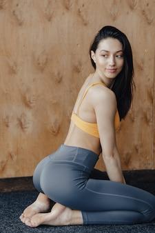 Giovane ragazza attraente di forma fisica che si siede sul pavimento vicino alla finestra sullo sfondo di una parete di legno, che riposa sulle lezioni di yoga