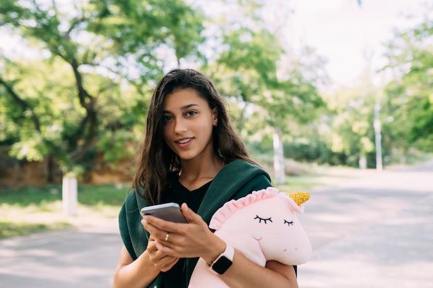 Giovane ragazza attraente digitando messaggi sul suo cellulare. guardando durante la digitazione di messaggi nella sua conversazione online.