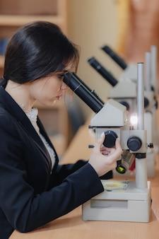 Giovane ragazza attraente emotiva seduto al tavolo e lavorando con un microscopio in un ufficio o pubblico moderno