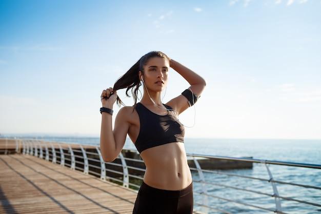 Giovane ragazza attraente fitness in esecuzione in riva al mare