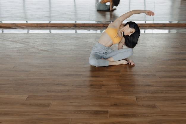 Giovane ragazza attraente su un pavimento di legno che fa yoga, stretching e relax