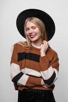 Giovane ragazza bionda abbastanza sorridente felice con cappello a tesa larga e labbra dipinte con rossetto rosso brillante, guardando la fotocamera