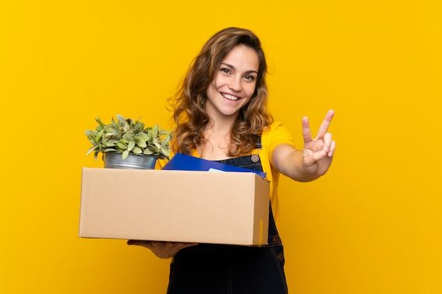 Giovane ragazza bionda che fa una mossa mentre raccoglie una scatola piena di cose che sorridono e che mostrano il segno di vittoria
