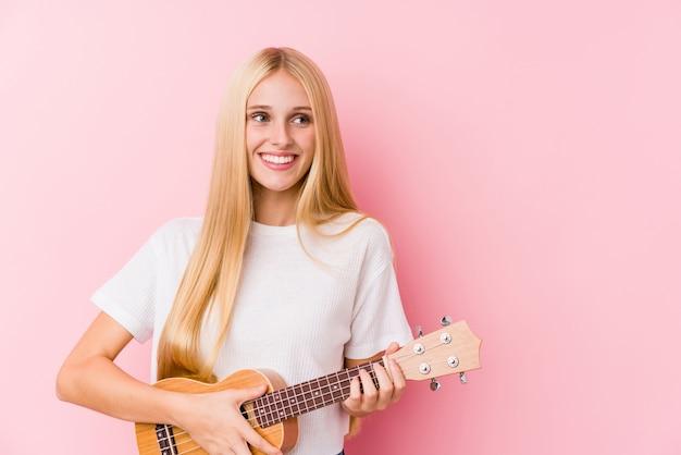 Giovane ragazza bionda che gioca ukelele che sorride sicuro con le braccia attraversate.