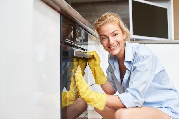 Giovane ragazza bionda che pulisce la cucina