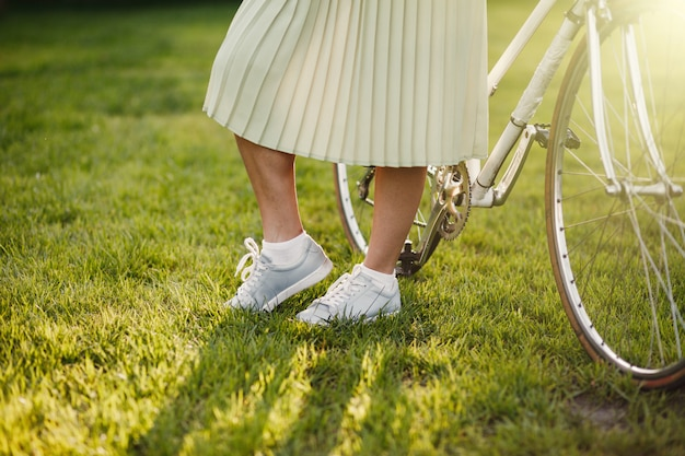 Giovane ragazza bionda con capelli lunghi che stanno vicino alla bicicletta bianca d'annata.