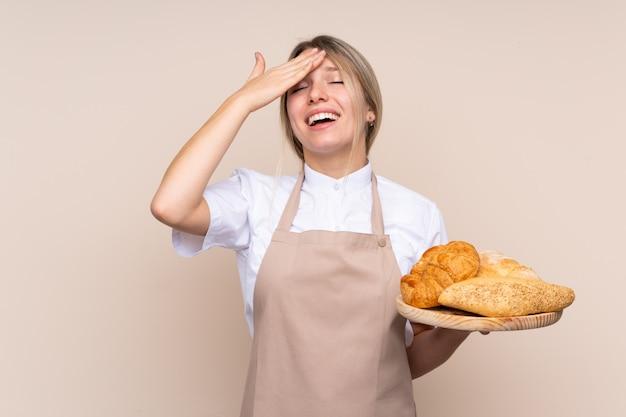 Giovane ragazza bionda con grembiule. il fornaio femminile che tiene un tavolo con diversi pani ha realizzato qualcosa e ha inteso la soluzione