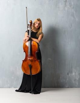 Giovane ragazza bionda con il suo violoncello sul fondo strutturato della parete