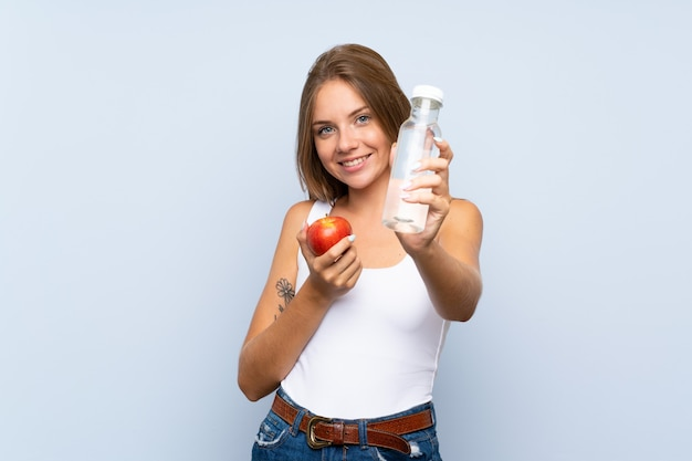 Giovane ragazza bionda con una mela e con una bottiglia di acqua sopra la parete isolata