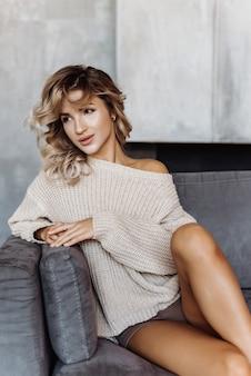 Giovane ragazza bionda del primo piano che si siede sul sofà in un maglione