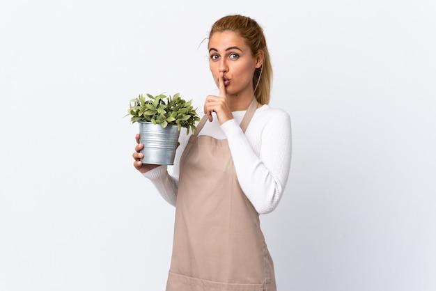 Giovane ragazza bionda della donna del giardiniere che tiene una pianta sopra la parete bianca che fa gesto di silenzio