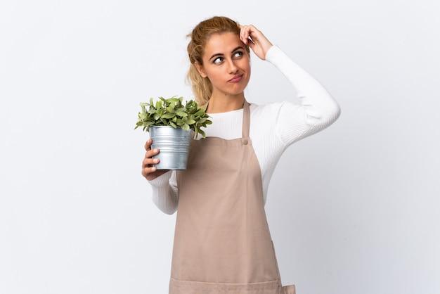 Giovane ragazza bionda della donna del giardiniere che tiene una pianta sopra la parete bianca che ha dubbi e con l'espressione confusa del fronte