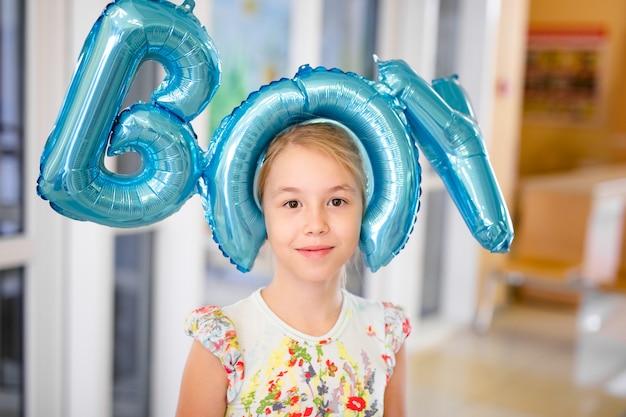 Giovane ragazza bionda felice con i baloons che sorride vicino in su