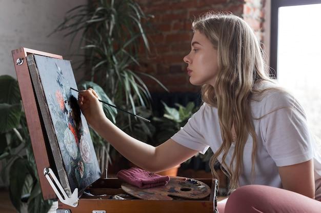 Giovane ragazza bionda graziosa con la spazzola e la tavolozza che si siedono vicino all'immagine del disegno del cavalletto in uno studio