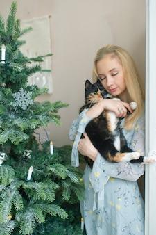 Giovane ragazza bionda in vestito elegante che tiene gattino divertente nella sala con l'albero di natale