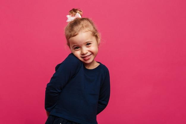 Giovane ragazza bionda timida che posa e che esamina la macchina fotografica sopra la parete rosa
