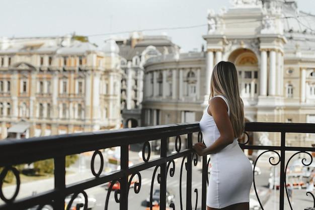 Giovane ragazza bionda vestita in abito corto bianco in buona forma è in piedi sul bordo del balcone e guardando sulla strada con vecchi edifici architettonici