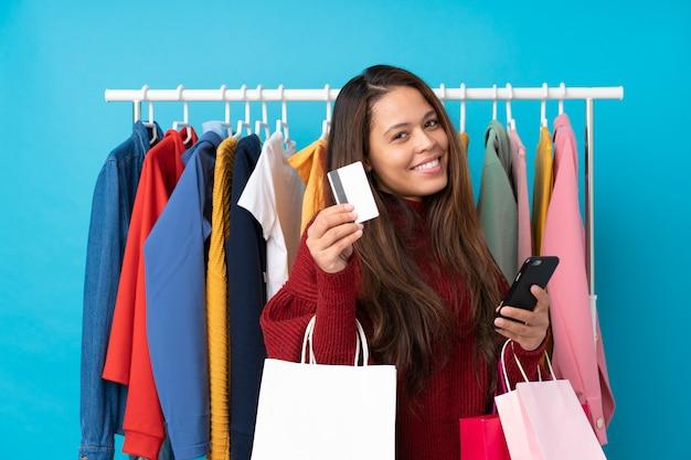 Giovane ragazza brasiliana con il sacchetto della spesa e con la carta di credito in un deposito sopra il blu isolato